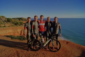 Team with wetsuits and bike